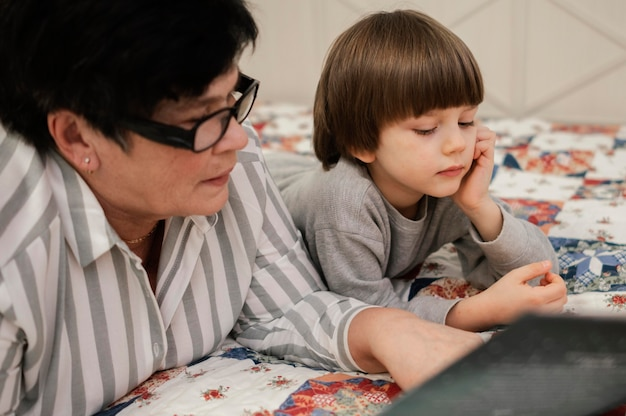 Grandmother and grandson at home reading