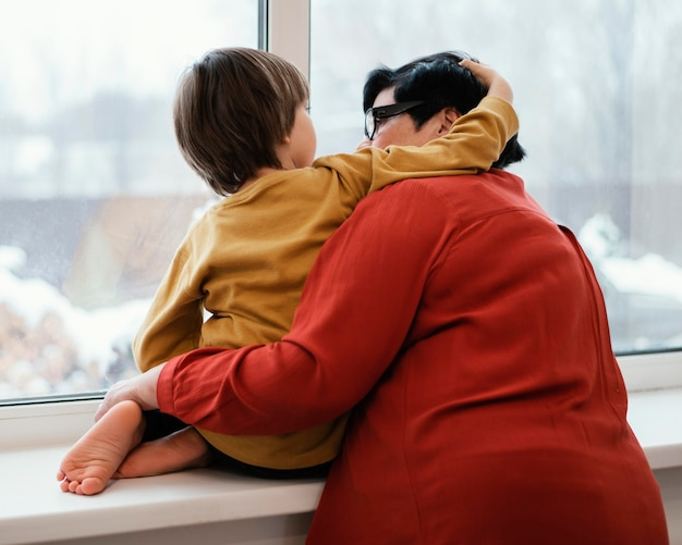 Grandmother and grandson looking through the window together