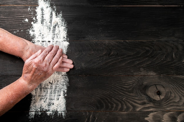 Grandmother hands of an old woman with flour in the shape of a heart with flour on dark black table, food recipe menu background. place for text. long banner format
