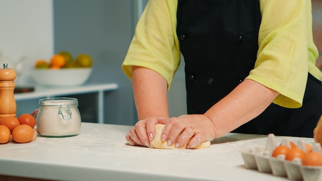 Grandmother hands preparing homemade cookies in modern kitchen kneading on the table. retired elderly baker with bonete mixing ingredients with wheat flour for baking traditional cake and bread