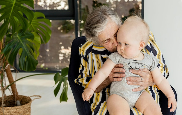 Grandmother holding grandchild at home