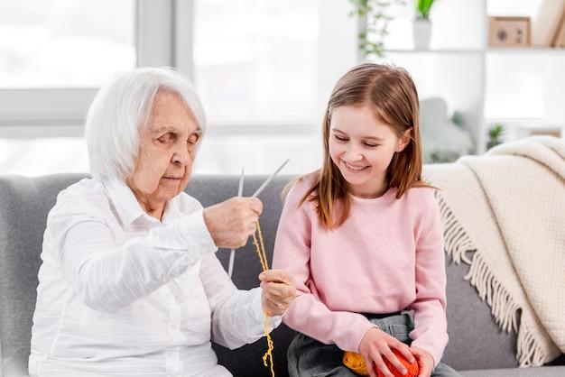 Бабушка держит спицы и учит вязать красивую внучку с клубком ниток в руках