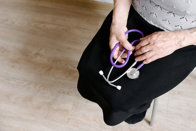The grandmother holds a stethoscope in hand