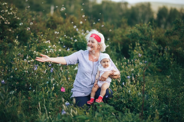 Grandmother hugging granddaughter in nature in sunny summer day