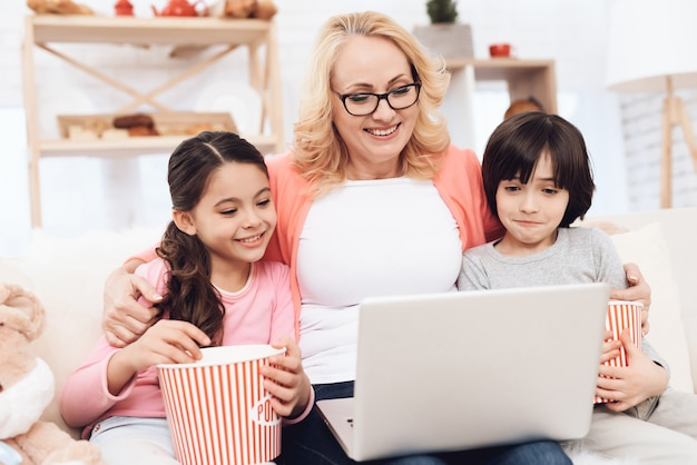 Grandmother hugging kids watching movie on laptop