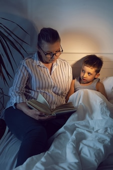 Бабушка в очках и белой рубашке читает книгу своему внуку, лежащему на кровати