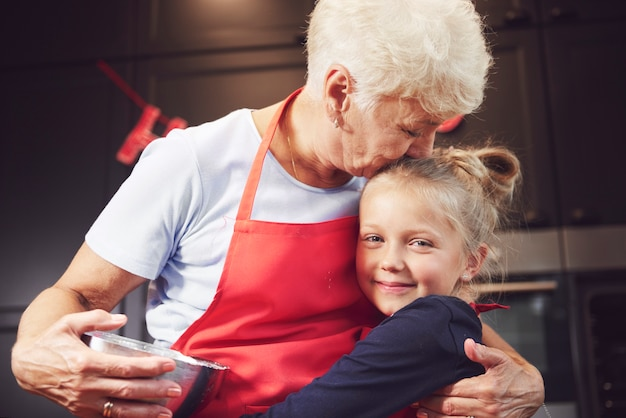 Бабушка целует и обнимает внучку