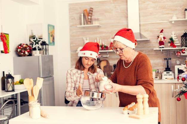 Бабушка учит племянницу печь вкусное печенье на рождество
