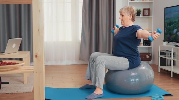 할머니는 거실에 있는 균형 공에 앉아 역기를 들고 있습니다. 홈 스포츠 건강한 생활 방식, 아파트, 활동 및 건강 관리에서 노인 피트니스 운동 운동에서 훈련하는 노인