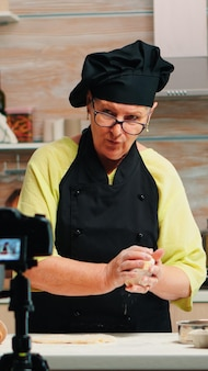Grandmother making cooking vlog, recording herself on camera. retired blogger chef influencer using internet technology communicating, shooting blogging on social media with digital equipment