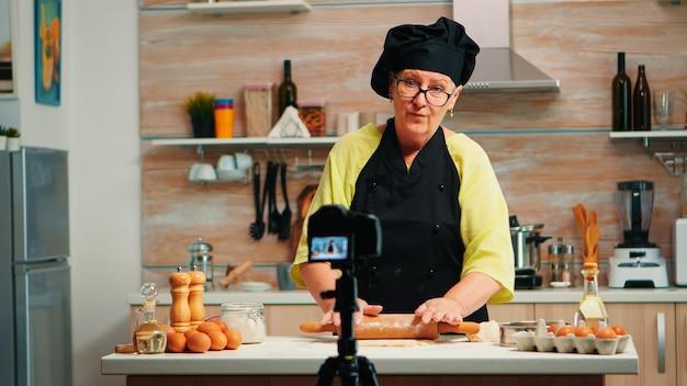Бабушка ведет видеоблог о кулинарии, снимает себя на камеру. блогер на пенсии, повар, влиятельный человек, используя интернет-технологии, общается, ведет блог в социальных сетях с помощью цифрового оборудования.
