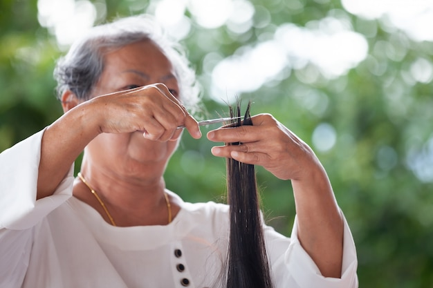 Grandmother making hairstyle to her granddaughter with scissor at home