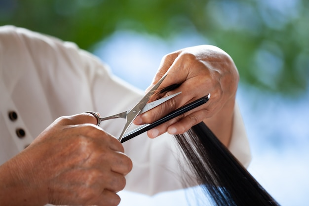祖母が自宅でハサミで孫娘に髪型を作る