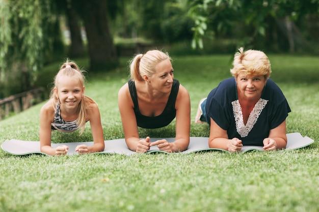 Бабушка, мама и ребенок вместе занимаются фитнесом на природе