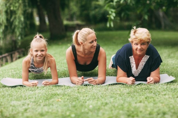 Grandmother, mom and child are doing fitness together in nature