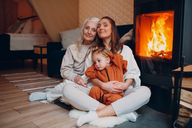 祖母の母と子が暖炉のお母さんと赤ちゃんの親の近くのソファに座って遊んでいます...
