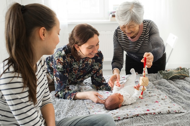 Grandmother and mother are happy baby. relatives play with a newborn