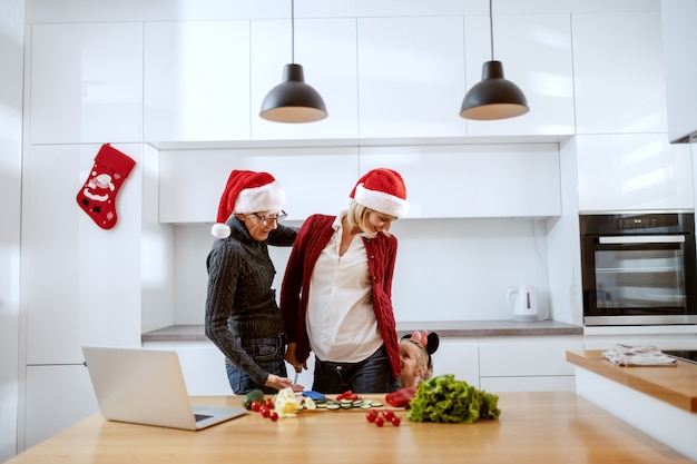 Grandmother, mother and little girl standing in kitchen and spending quality time together. on kitchen counter are vegetables and laptop. family time for christmas concept.