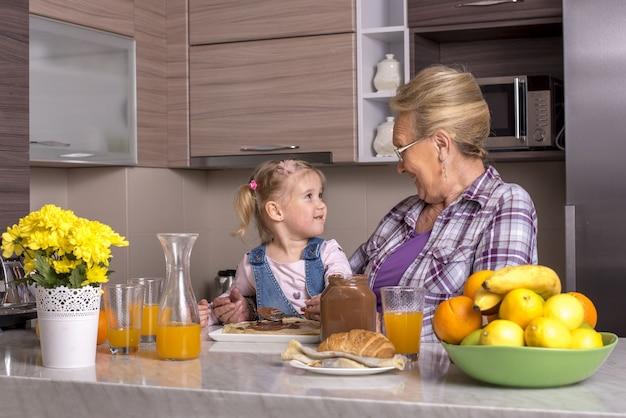 キッチンで孫娘と遊ぶ祖母