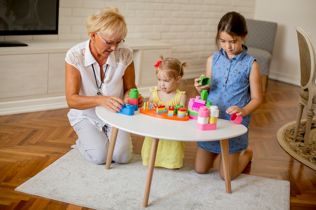 Grandmother playing with little granddaughters in the room
