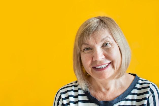 祖母の肖像画。幸せな笑顔の白髪のブロンドのシニア女性が黄色の壁に隔離