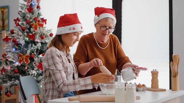 祖母がストレーナーに小麦粉の材料を入れて孫娘に説明する