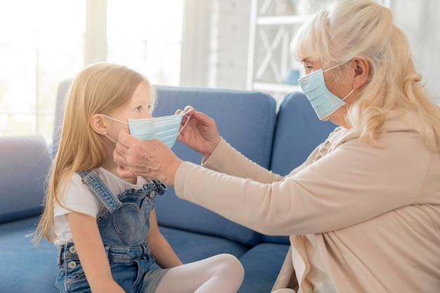 Grandmother putting mask to girl