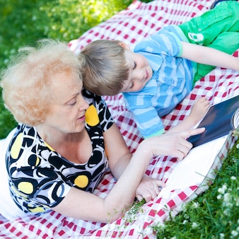 Grandmother reading book to her grandson