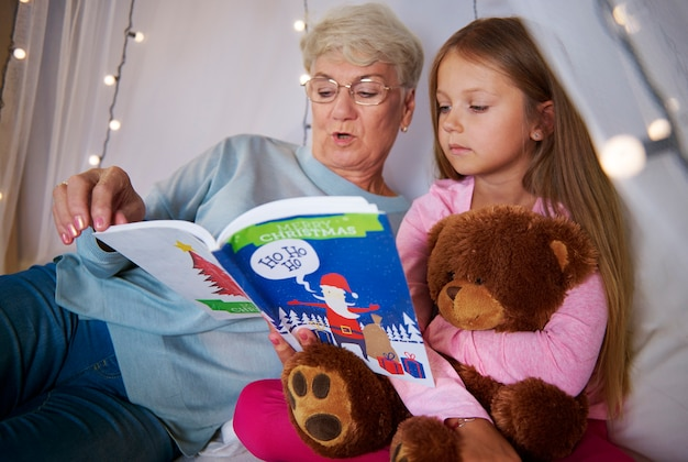 Grandmother reading book out to her granddaughter