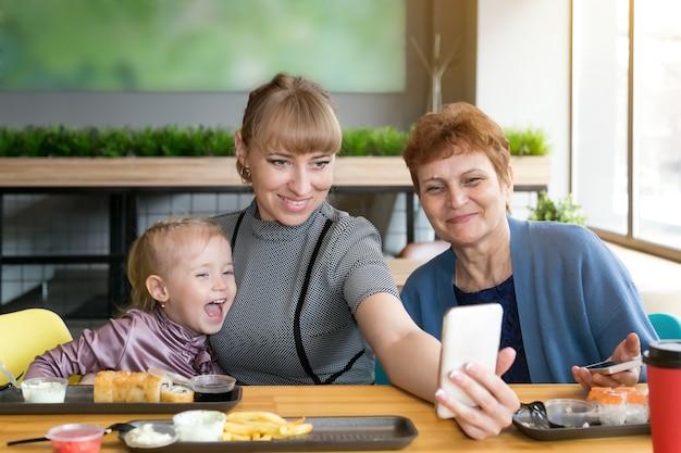 Бабушка дочь и внучка фотографируются по телефону в кафе.
