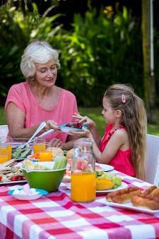 孫娘に食べ物を提供する祖母