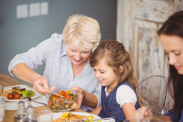 Grandmother serving granddaughter while having breakfast