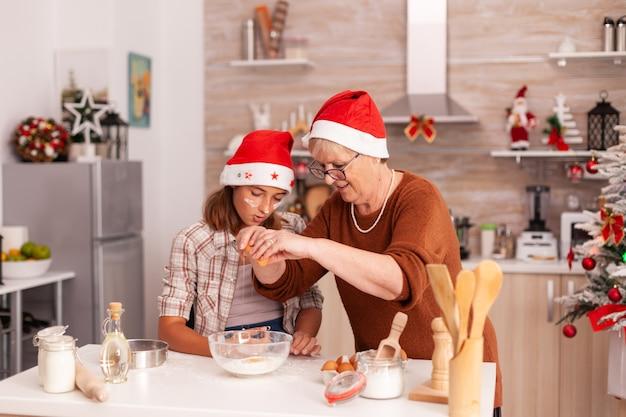 クッキー生地の作り方を子供たちに示すおばあちゃん