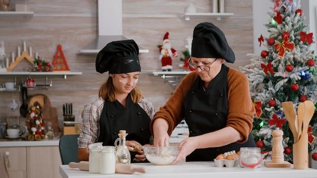 祖母が孫に伝統的なクッキーデザートの作り方を教えてくれる