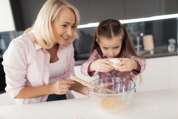 Grandmother smile. girl breaks egg into bowl.