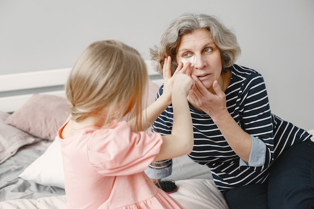 Grandmother spending time with her granddaughter in the bedroom