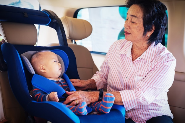 Grandmother takes care about her little granddaughter in a car, helps her and cheers up