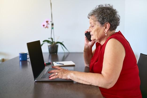 自宅の側面図でラップトップを使用しながら電話で話している祖母