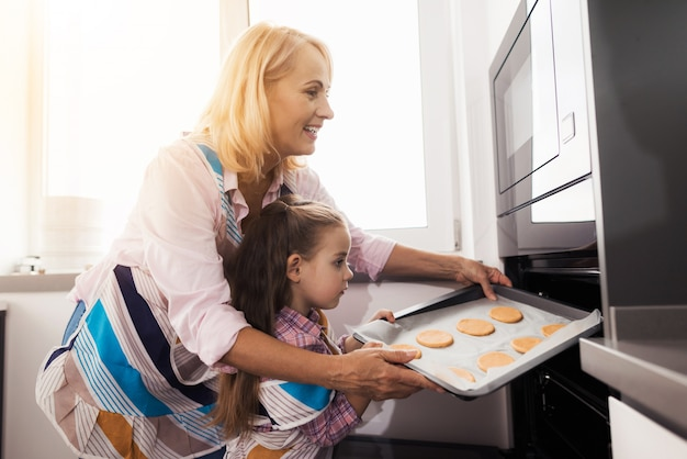 Grandmother teaches the girl to make homemade cookies.