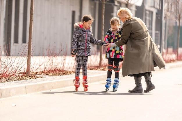 祖母は孫娘にローラースケートを教えます。