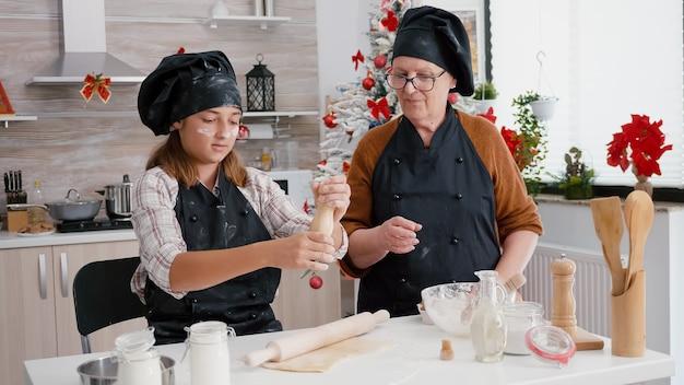Grandmother teaching granddaughter how prepare delicious xmas gingerbread dessert