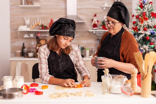 Grandmother teaching granddaughter how to prepare homemade cookies