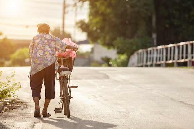 The grandmother walking with old bicycle on the street