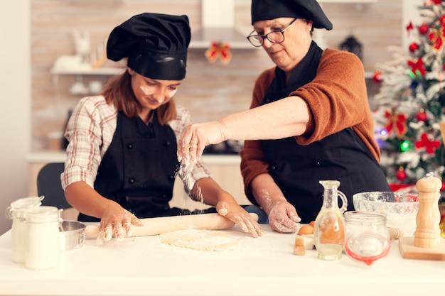 小麦粉を広げるクリスマスの日にエプロンを着ている祖母