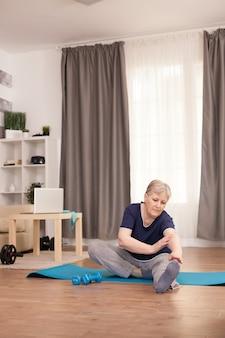 Бабушка, ведущая здоровый образ жизни, тренируется на растяжке