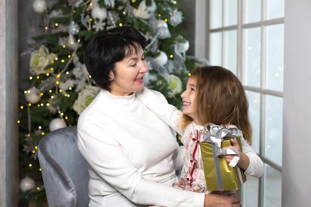 Бабушка с маленькой девочкой на фоне елочных игрушек и большого окна