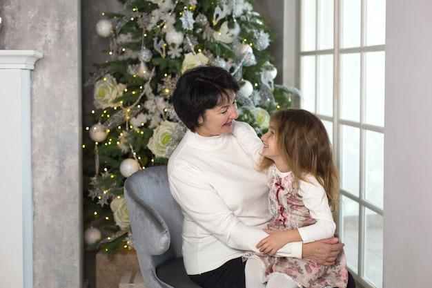 クリスマスの飾りと大きな窓を持つ小さな女の子と祖母。家族の休日、感情、ギフトボックス。おばあちゃんの膝の上に孫娘。新年