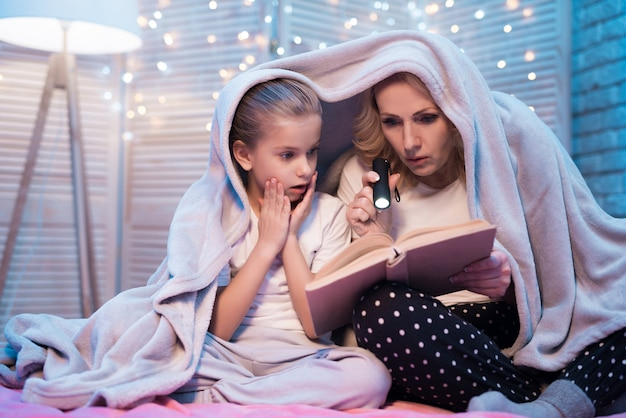 Grandmother with girl are reading book at night at home.