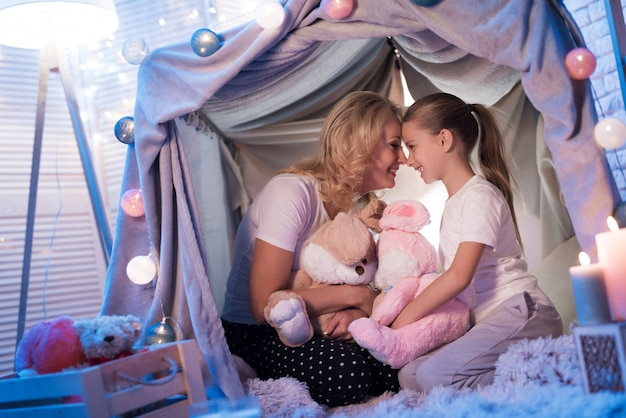 Grandmother with girl in blanket house at night at home