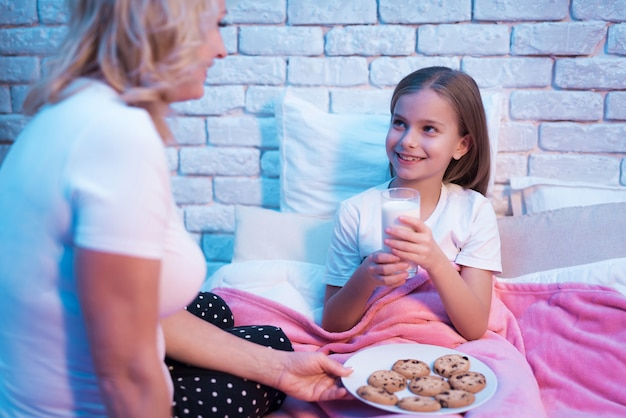 Grandmother with girl cookies and milk in bed